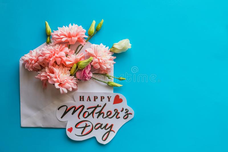 Festive composition with text HAPPY MOTHER`S DAY on candy blue background.Flowers in envelope.Greeting Card with Spring stock photo