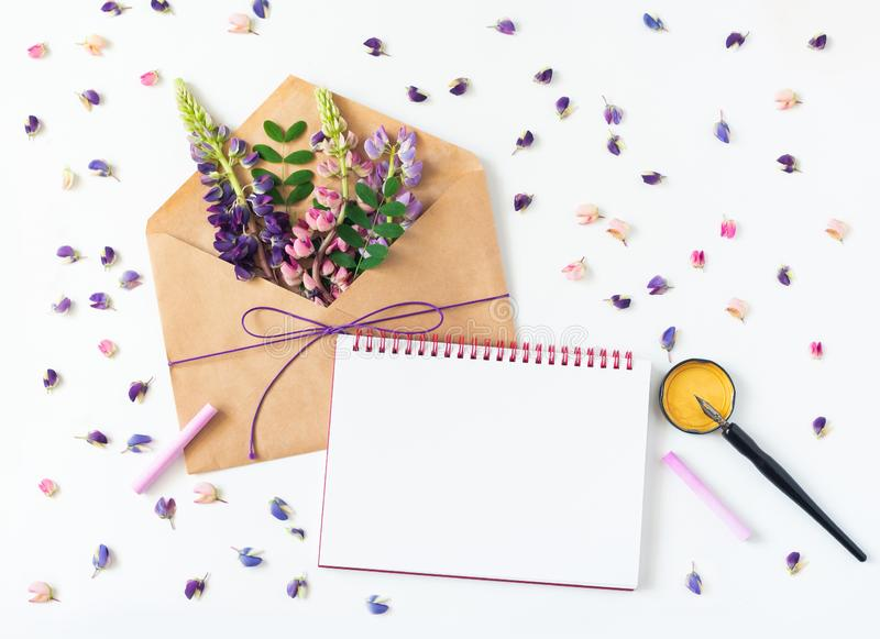 Festive composition: on a white table lies an envelope, notebook, fountain pen and flowers. Concept of Mother`s Day and stock image