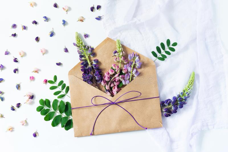 Festive composition: on a white table lies an envelope, notebook, fountain pen and flowers. Concept of Mother`s Day and royalty free stock image