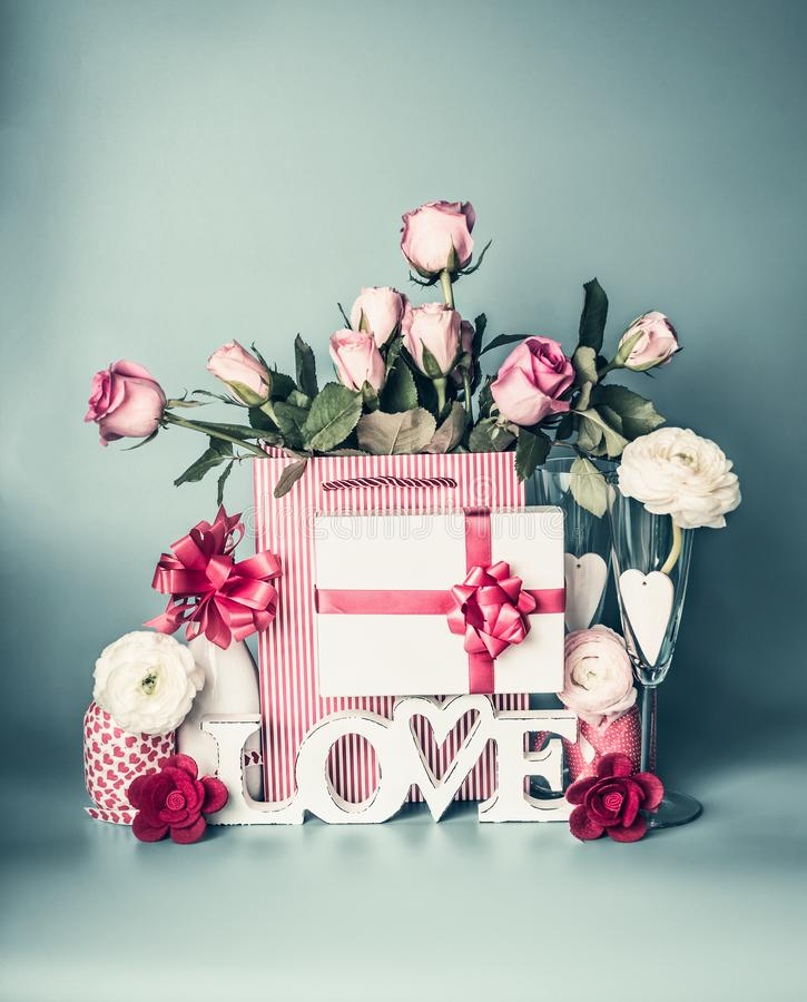 Festive composition with word LOVE greeting box with red ribbon, shopping bag with roses flowers, packing decorations. Bottle of champagne, glasses and hearts stock photos