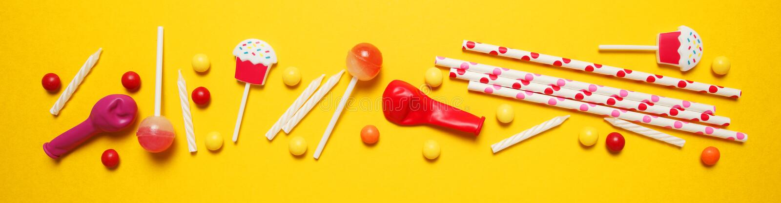Festive decor for children`s birthday. Sweet multicolored candies, balloon, straws.  stock photos