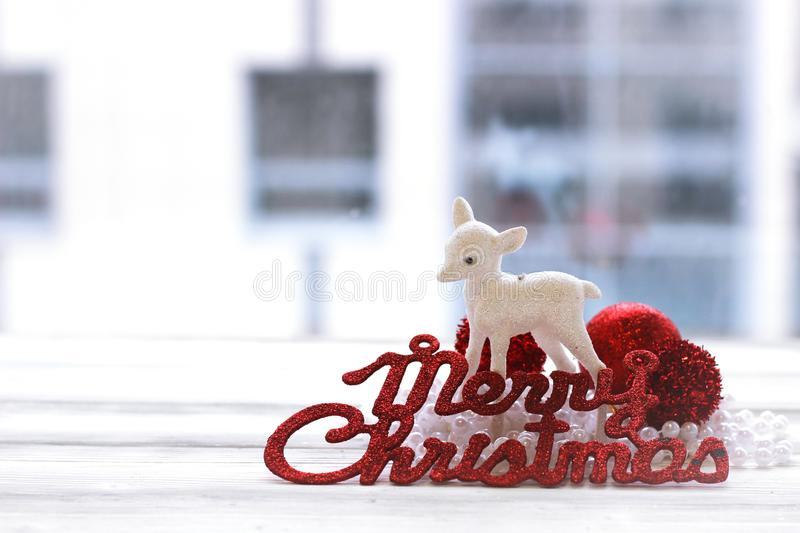 Festive decoration, christmas balls, statuette of deer. And inscription: Merry Christmas against window royalty free stock image