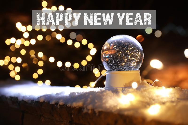 Festive decoration with snow on parapet and message HAPPY NEW YEAR against blurred background. stock photos