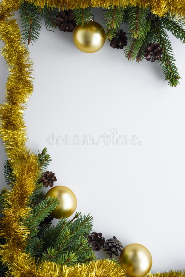Festive decorations as christmas frame with copy space. Conifer branches, cones, gold baubles and tinsel. Vertical greeting card. Festive decorations arranged as royalty free stock photos