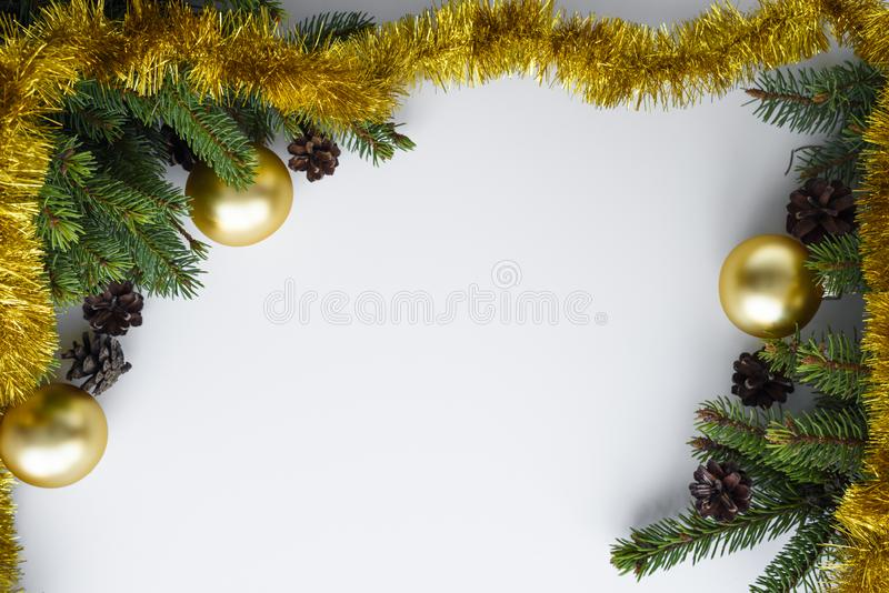 Christmas frame with copy space for wishes. Conifer branches, cones, gold baubles and tinsel. Greeting card. Festive decorations as a christmas frame with copy stock photos