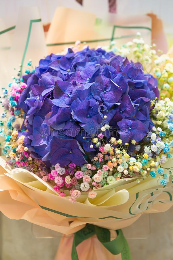 Festive delicate bouquet of blue hydrangea and colorful gypsophila, selective focus. Floristics and bouquets, greetings and stock photos