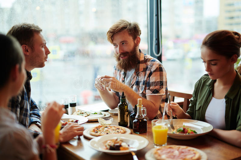 Festive Dinner in Restaurant. Group of friend enjoying each others company while having festive dinner in restaurant with panoramic windows, waist-up portrait royalty free stock images