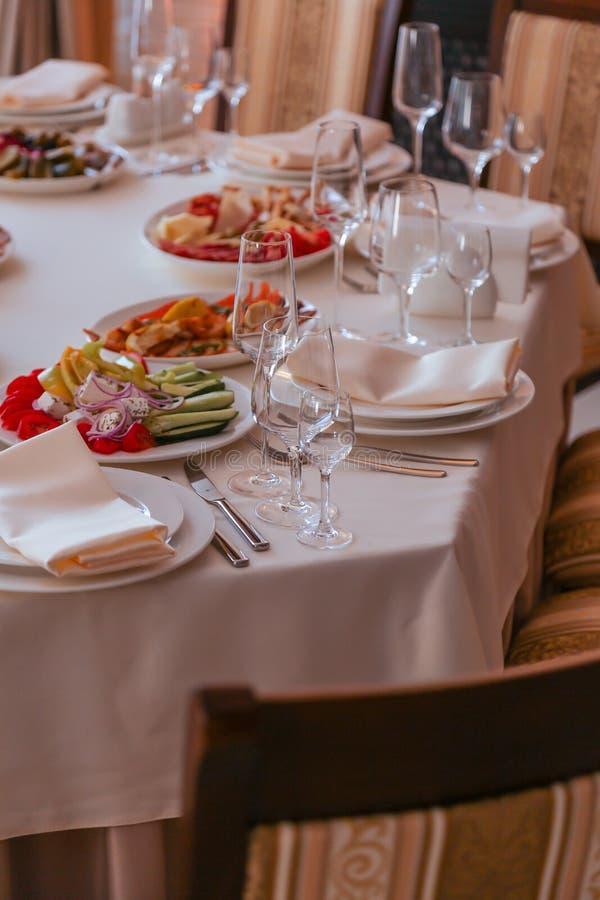 Festive dinner table inside a restaurant. Festive dinner table  and starters inside a restaurant royalty free stock images