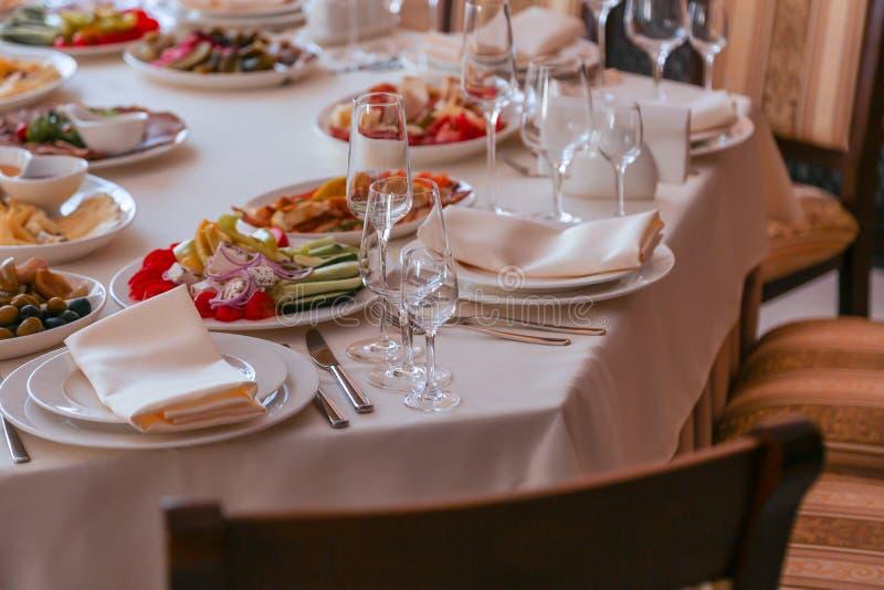 Festive dinner table inside a restaurant. Festive dinner table  and starters inside a restaurant royalty free stock photography