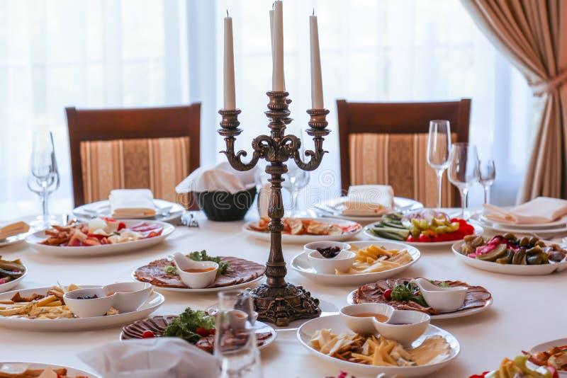 Festive dinner table inside a restaurant. Festive dinner table  and starters inside a restaurant stock photography