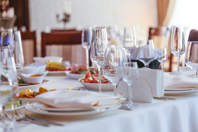 Festive dinner table inside a restaurant. Festive dinner table  and starters inside a restaurant stock photos