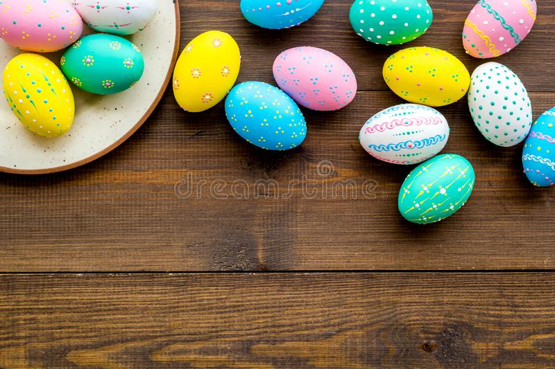 Festive Easter table. Colorful Easter eggs on plate on dark wooden background top view copy space stock image