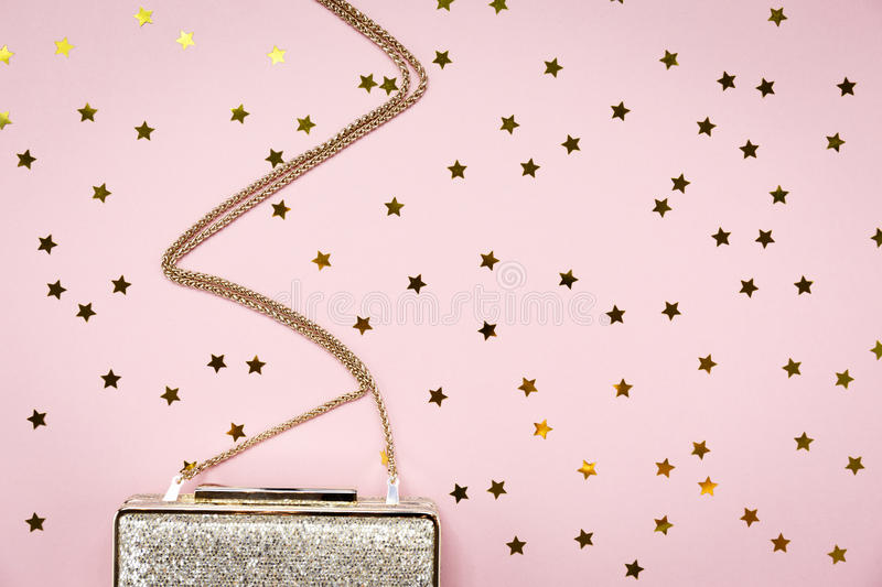 Festive evening golden clutch with star sprinkles on pink. Holiday and celebration background. Luxury accessories and party royalty free stock images