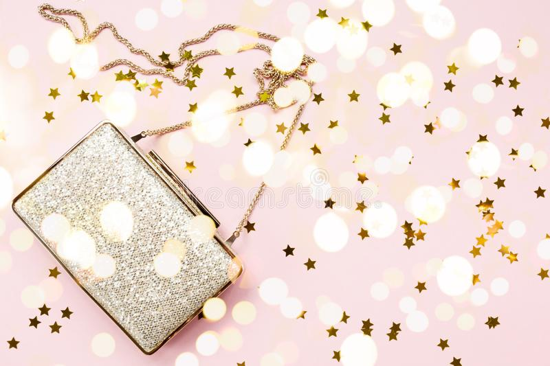 Festive evening golden clutch with star sprinkles on pink. Holiday and celebration background. Luxury accessories and party royalty free stock photography
