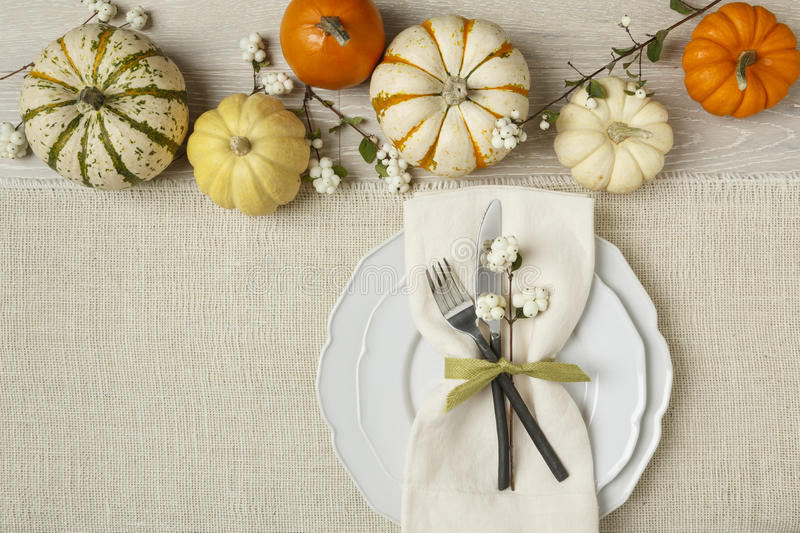 Festive fall autumn Thanksgiving table setting with natural botanical decorations and white fabric tablecloth background stock image