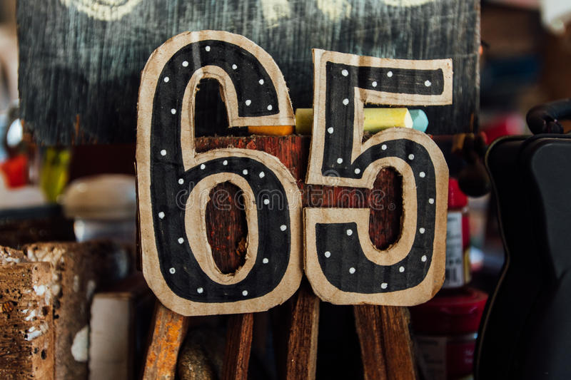 Festive figures are 65 for the birthday. Cardboard, handmade. Festive figures are 65 for the birthday. Cardboard, handmade, on a stand royalty free stock image