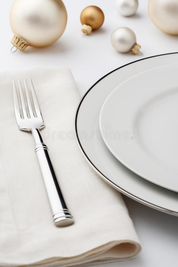 Festive fine dining Christmas dinner table setting place setting. With high quality classic style white china porcelain dishes, linen cloth napkin, silverware royalty free stock images