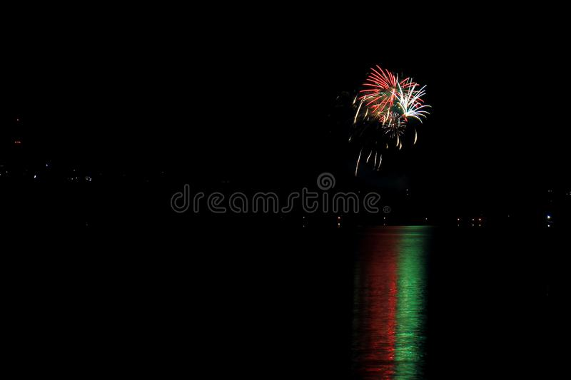 Festive fireworks over the night city. Reflected in the lake royalty free stock images