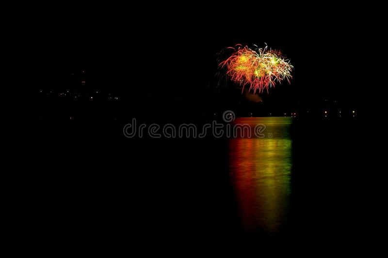 Festive fireworks over the night lake. Festive fireworks over the night city reflected in the lake stock photos