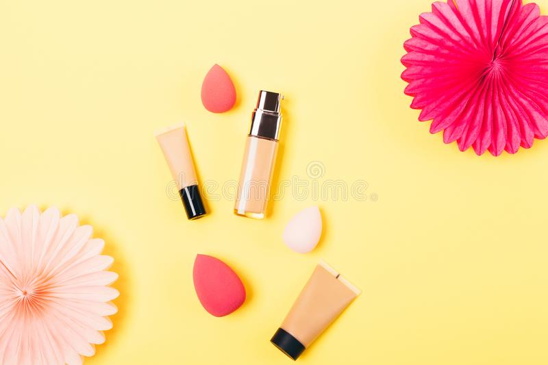 Festive flat lay arrangement makeup products. Cosmetic foundation next to egg shaped sponge applicators and tissue paper decorations, top view on yellow stock images
