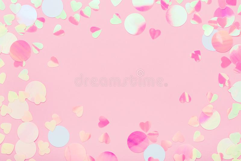 Festive frame of iridescent multicolored confetti sparkling on pink pastel background. royalty free stock photos