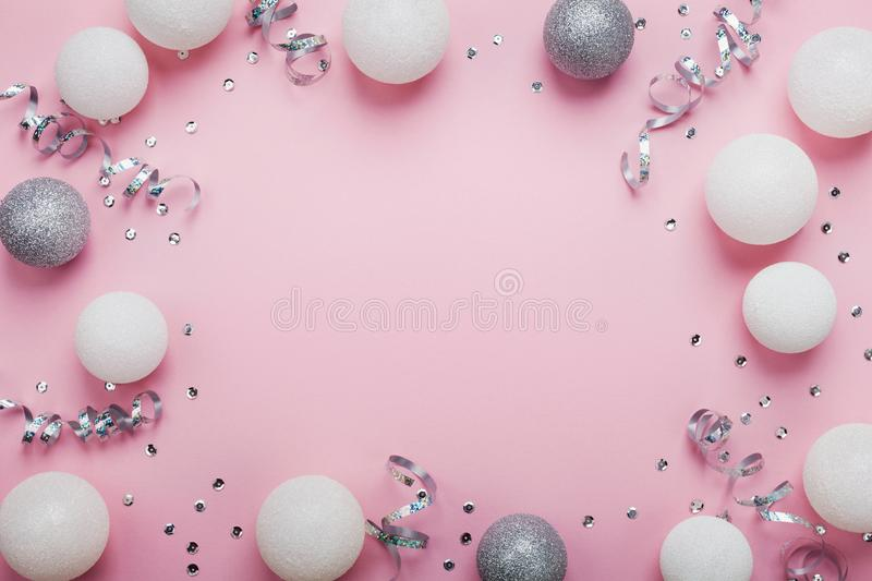 Festive frame made of christmas balls and sequins on pink table top view. Fashion background. Flat lay. Party mockup. Festive frame made of christmas balls and royalty free stock photography