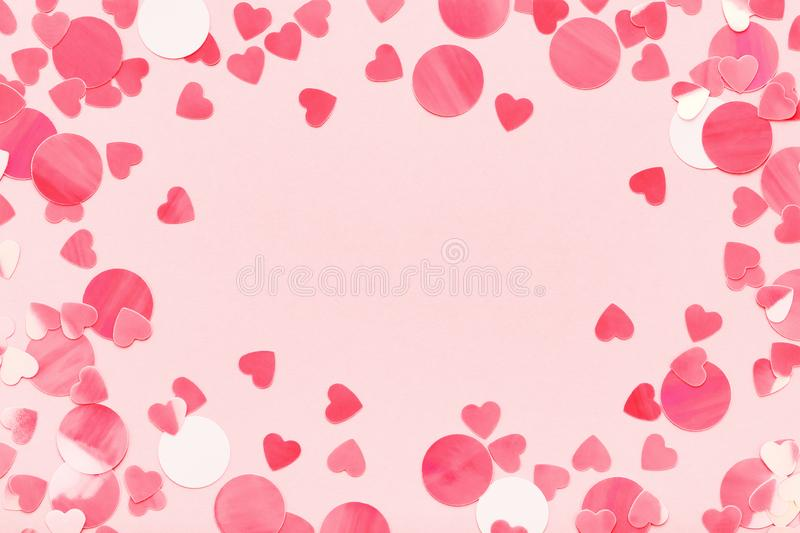 Festive frame of red hearts confetti on pink pastel background love Valentine`s Day. royalty free stock photos