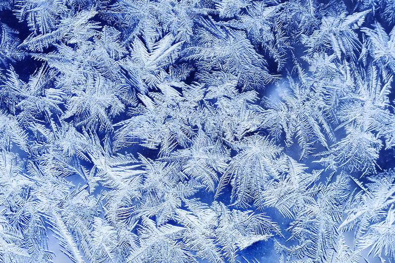 festive frosty pattern with white snowflakes on a blue background on glass stock photography