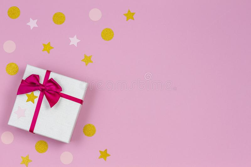 Festive gift box with satin bow and glitter confetti sparkles on light pastel pink background. Top view. Festive gift box with satin bow and glitter confetti stock photos