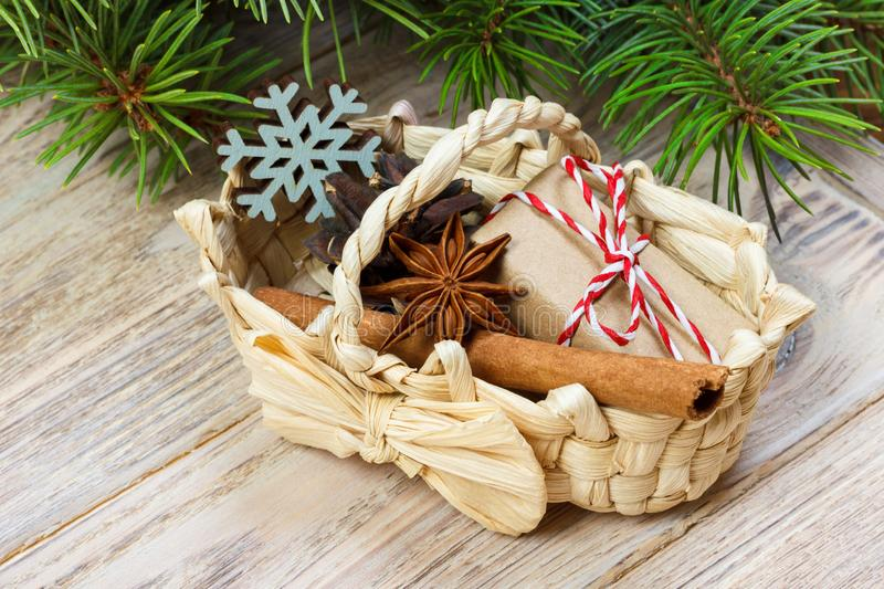 Festive Gifts with boxes, star anice, basket, cinnamon and snowflake on Wooden Background. Christmas Presents with copy space stock photo