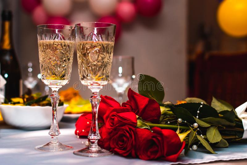 Festive glasses with sparkling champagne on the table of the newlyweds with a bouquet of red roses, selective focus, wedding royalty free stock photography