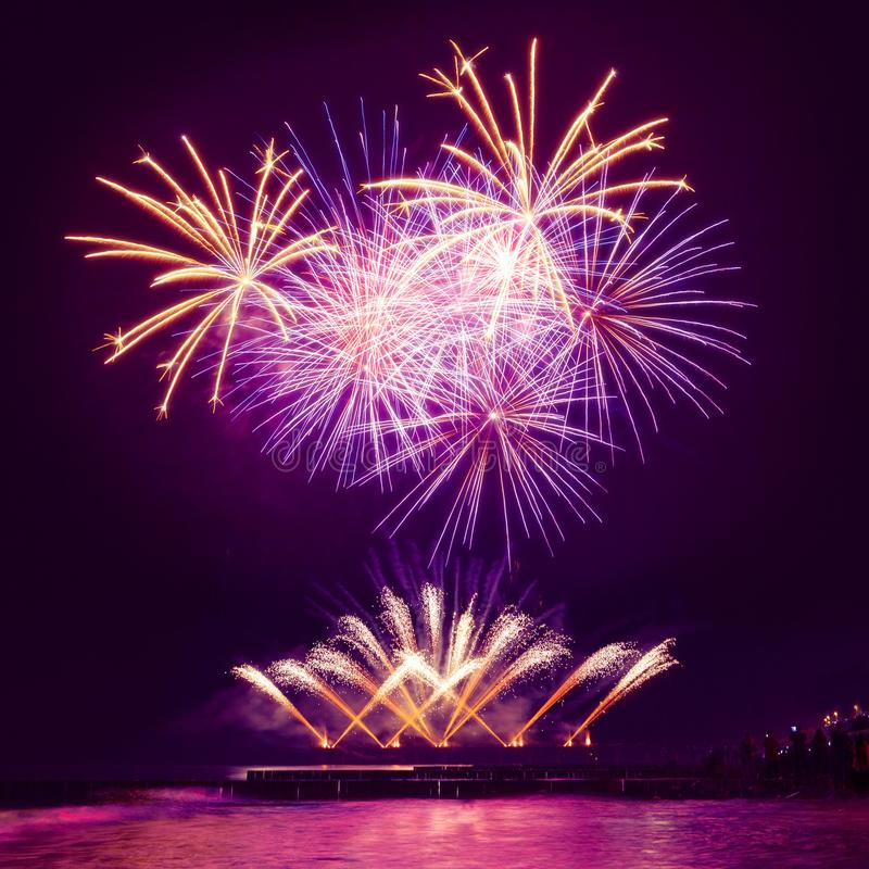 Festive, gold and blue fireworks on the sea. stock photo