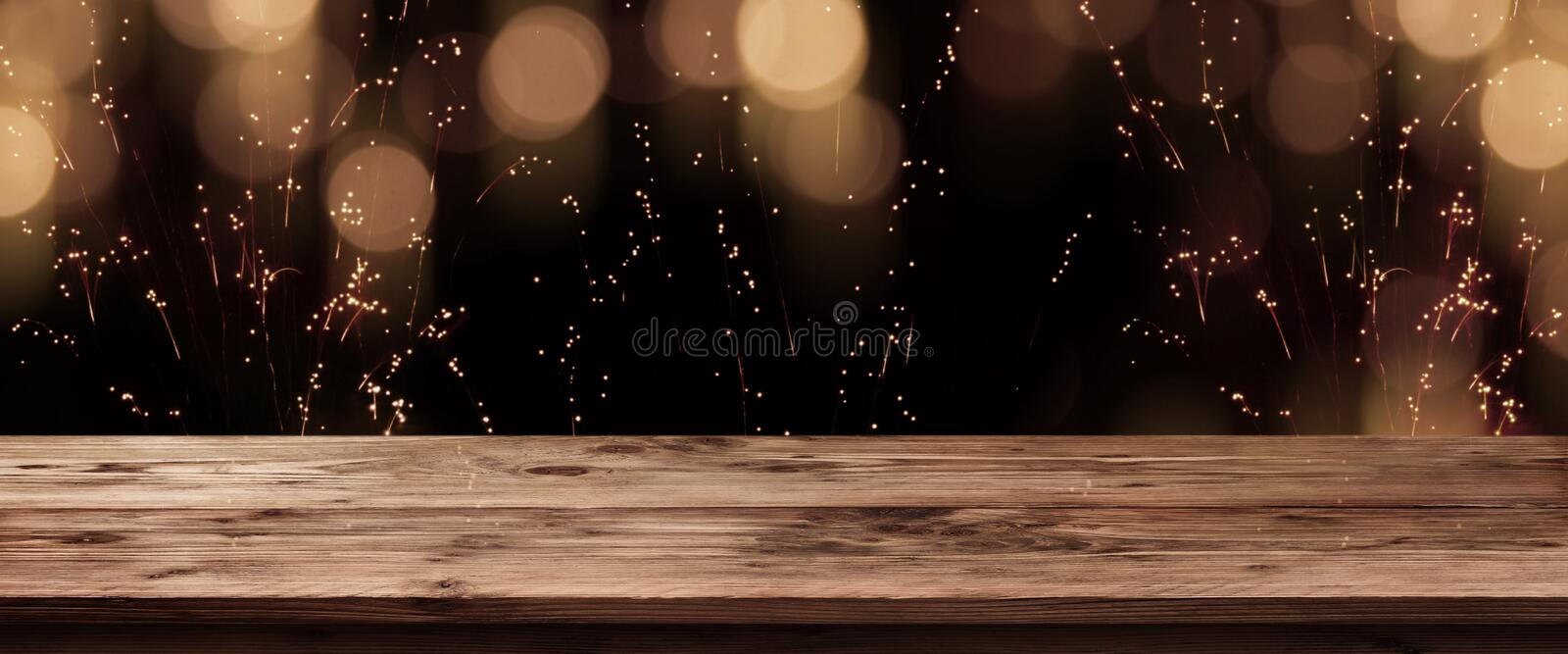 Festive golden bokeh with wooden table royalty free stock photo