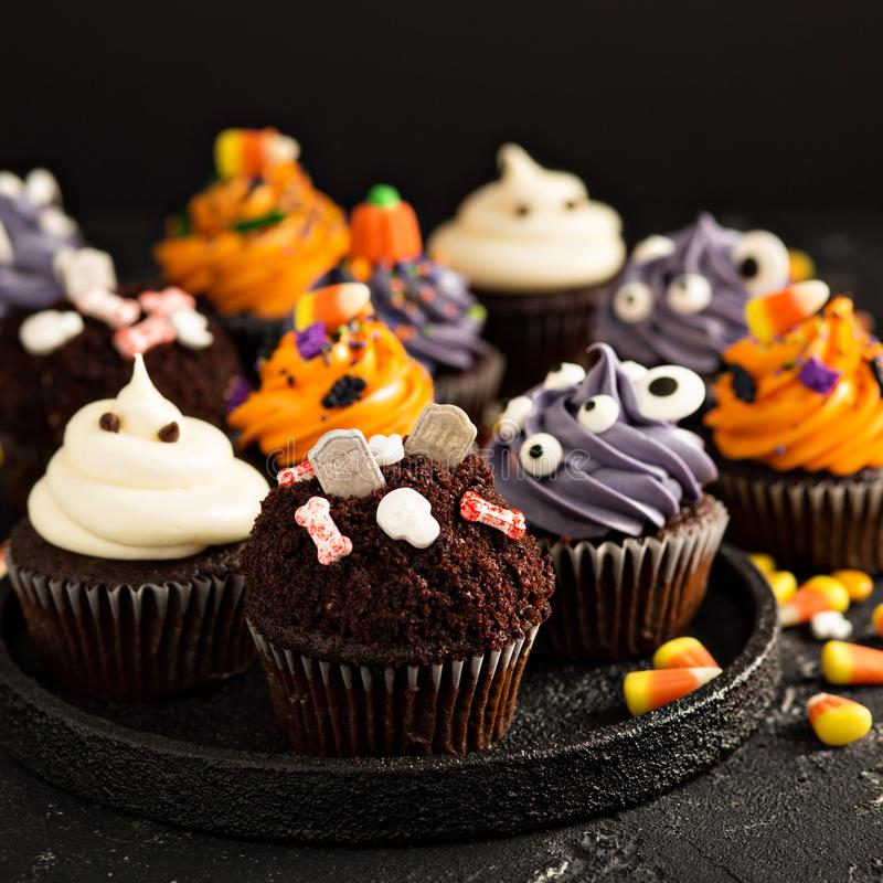 Festive Halloween cupcakes and treats. Decorated with sprinkles and candy royalty free stock photos