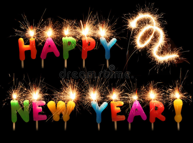 Festive Happy New Year sparkling candles. Festive words Happy New Year fron colorful candles with sparklers isolated on black stock images