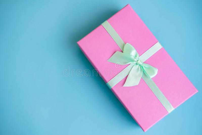 Festive holiday New Year and Christmas blue background with pink gift box. Concept of carnival, birthday, party. Flat royalty free stock image