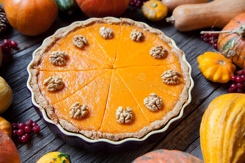 Festive Homemade Delicious Pumpkin pie with walnuts made for Thanksgiving and halloween, top view. Autumn composition. stock photo