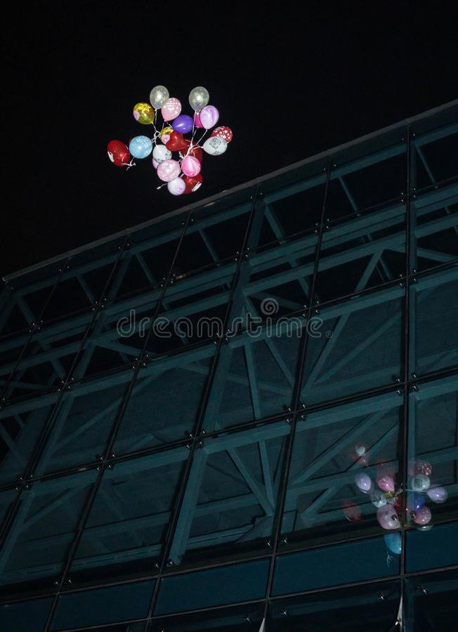 Festive inflatable balloons flying against night sky and their reflection stock images