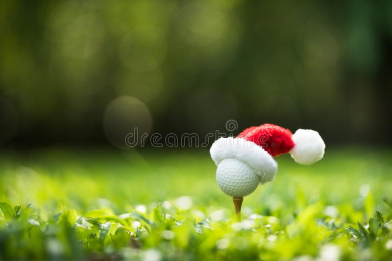 Festive-looking golf ball on tee with Santa Claus` hat royalty free stock photos