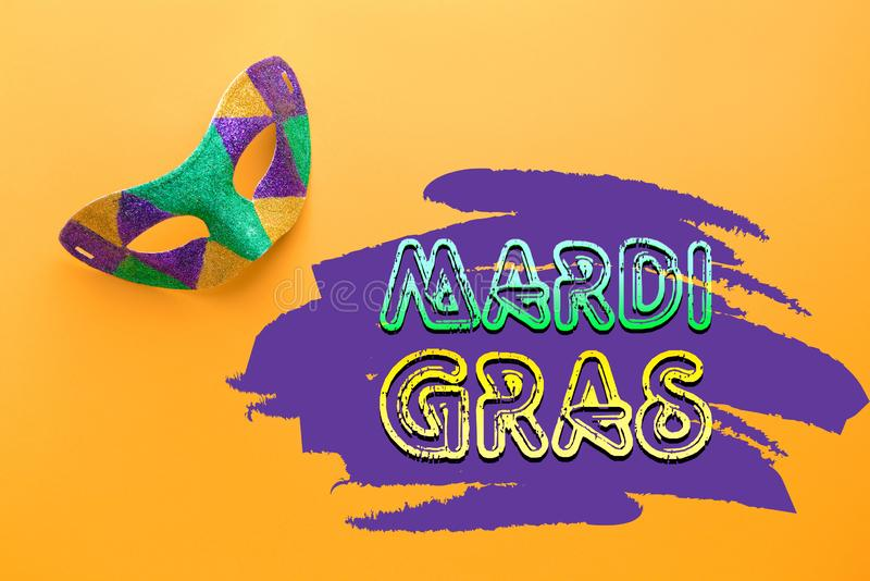 Festive mask with text MARDI GRAS (also known as Fat Tuesday) on color background royalty free stock photography