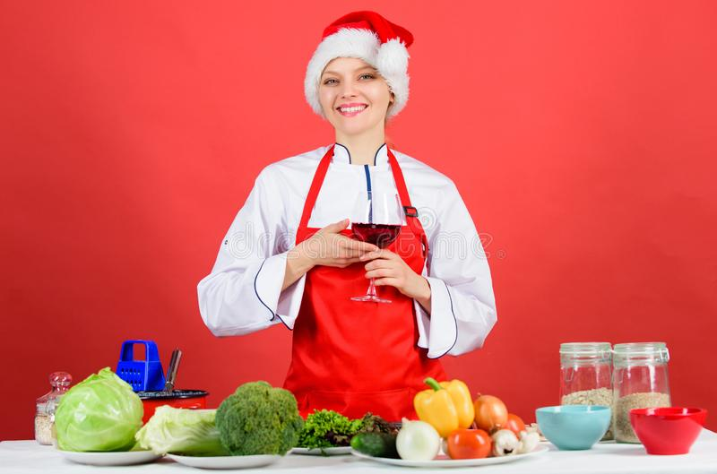 Festive menu concept. Christmas dinner ideas. Christmas menu. No stress. Woman chef cooking wear santa hat drink wine. Best christmas recipes. Enjoy easy ideas stock image