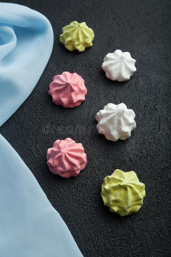 Festive meringue cookies of different colors on black background.  stock images