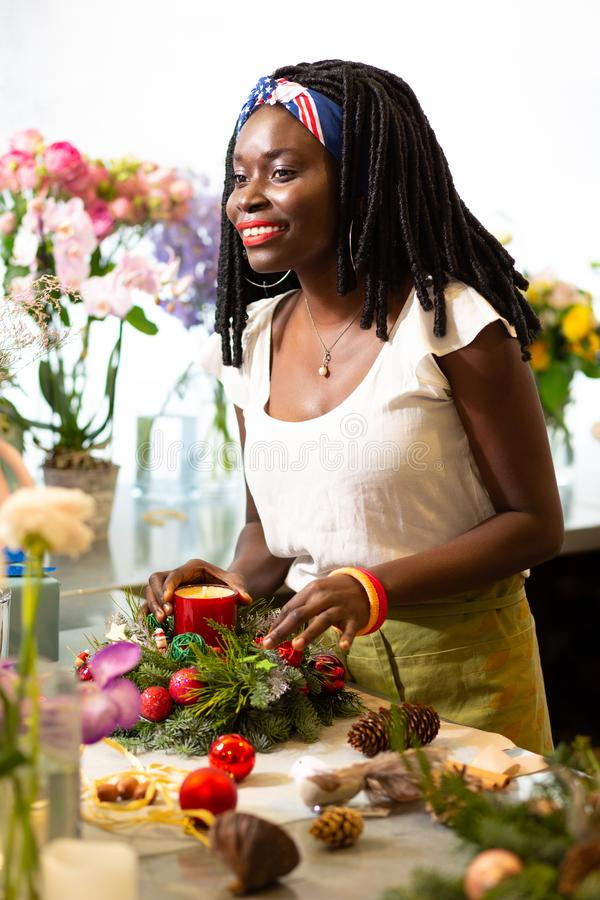 Amazing international woman working in floral boutique. Festive mood. Kind decorator expressing positivity while putting candle into wreath stock photos