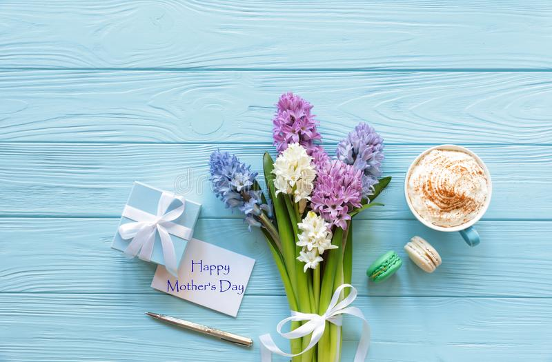 Festive morning cappuccino with macaroons, beautiful bouquet of hyacinth flowers in pink, blue, white, violet colors, gift box, stock photos