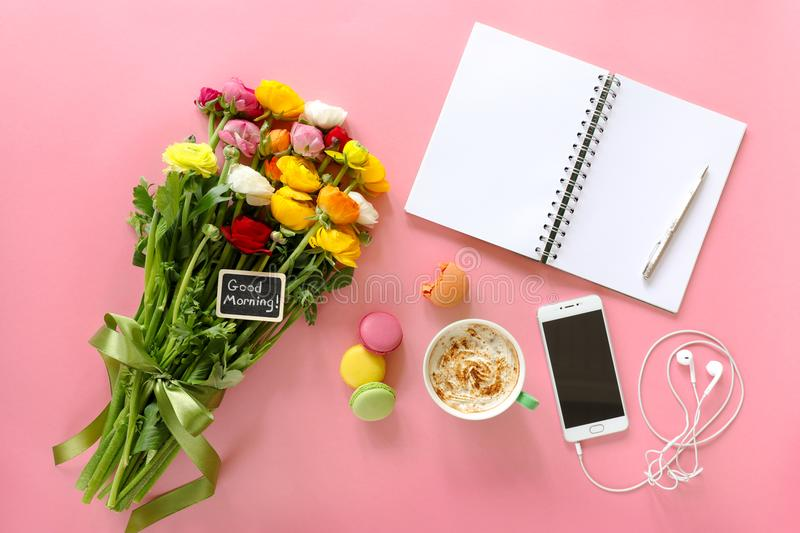 Festive morning concept buttercup flowers with note good morning, cup of cappuccino, cake makaron, mobile with headphones, noteboo. Festive morning buttercup stock photos