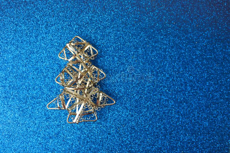 Festive New Year Christmas happy blue shiny joyful background with a small toy metal iron silver homemade Christmas tree. Flat lay. Top view. Holiday royalty free stock images