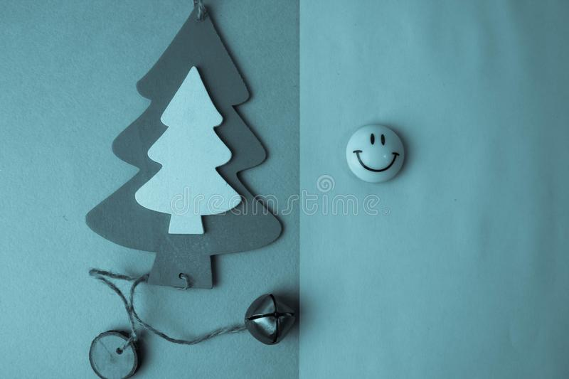 Festive New Year`s Christmas small toy wooden homemade tree and a round smiling emoticon. Flat lay. Top view. Holiday decorations. Festive New Year`s Christmas stock photo