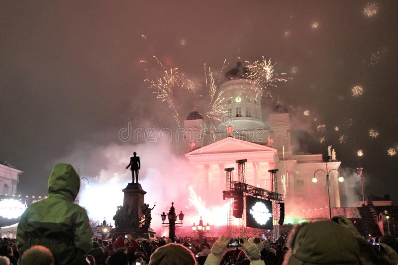 Festive New Year`s fireworks on the main square of Helsinki on January 1, 2013. People celebrating the New Year, bright flashes of fireworks in the dark purple stock photography
