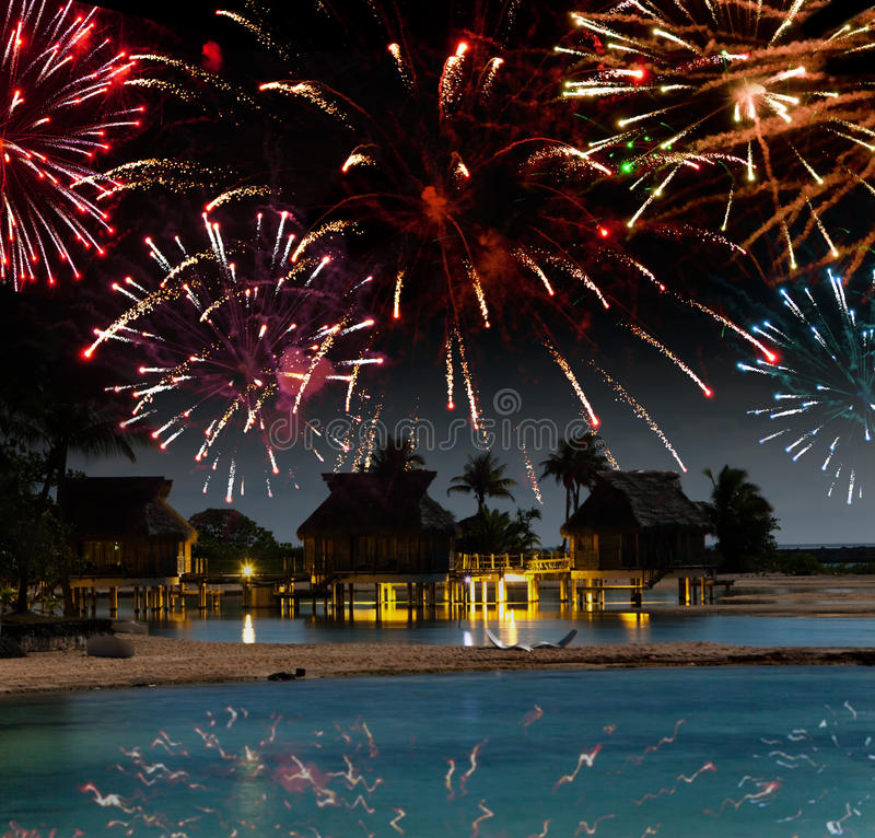 Festive New Year's fireworks over the tropical island. Night tropical landscape stock photo