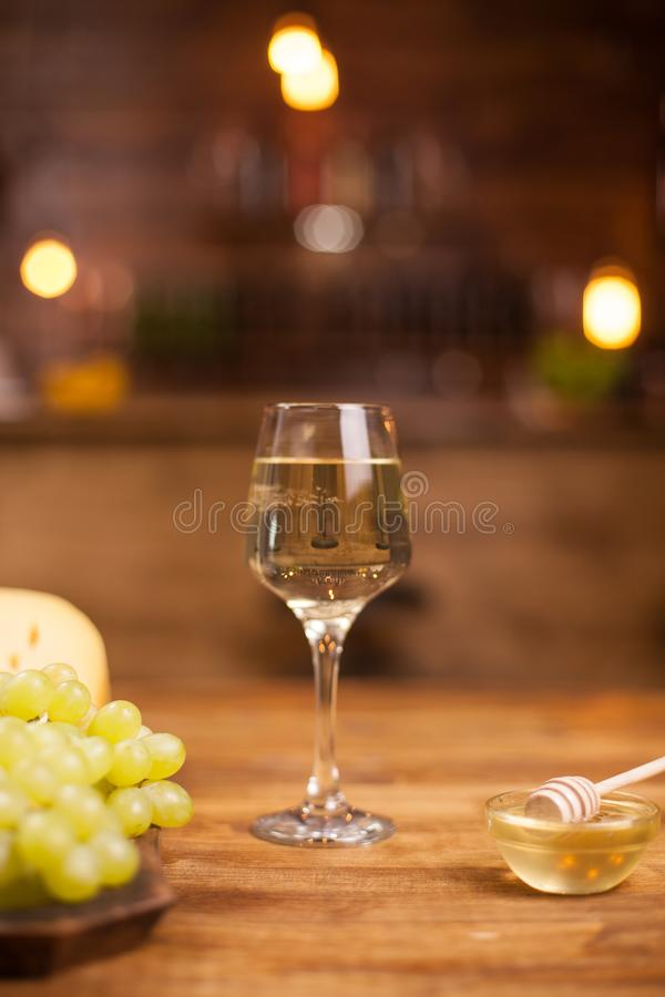 Festive night with wine degustation and cheese in a vintage pub. Delicious grapes. Great honey stock image